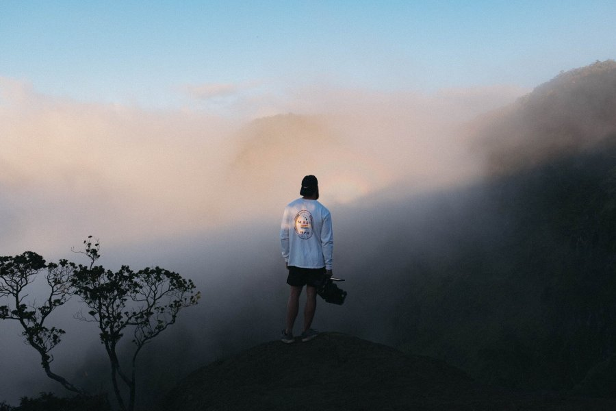 man on hill looking at fog